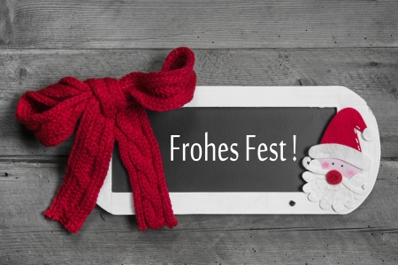 Red bow on menu board with Merry Christmas - Frohes Fest - german message on wooden background photo