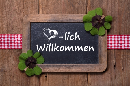 Old menu board with welcome message in german - clovers and ribbon on wooden background photo