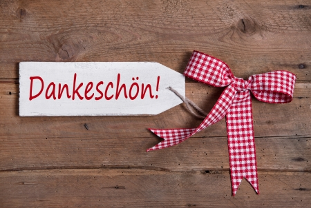 Thank you in german language - Dankeschön  Old board with text and a red checked ribbon  photo