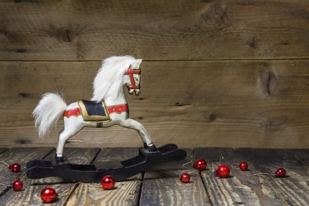 christmas toys: Vintage - old wooden rocking horse on a wooden old board for a christmas card with red balls - classic decoration