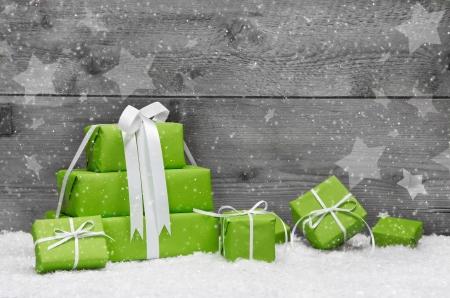 緑のクリスマスのグリーティング カードやクーポン、バウチャーの灰色の木製の背景に雪を呈する