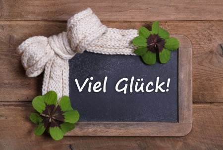 Menu board with good luck message in german - clovers and white bow on wooden background Stock Photo - 22931942