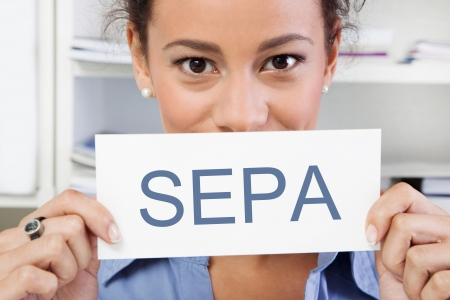 bank transfer: Young woman looking at camera holding a SEPA sign isolated on white