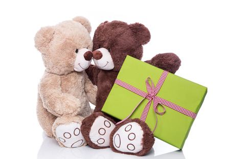 Christmas  Two isolated teddy bears in love holding a green present photo