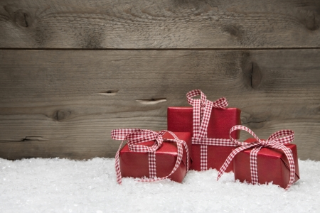 snow background: Red Christmas presents with checkered bows on grey wooden