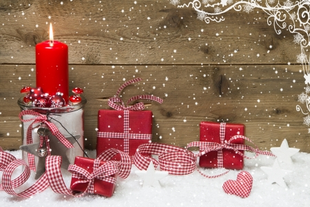 atmospheric: Atmospheric Christmas card with red burning candle and presents on snowflake wooden