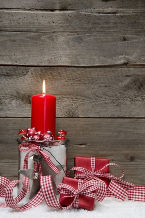 Wooden Christmas with a red candle and a gift box on snow