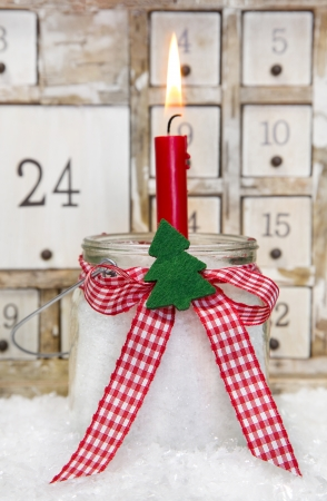 One red advent candle with a red checkered bow for christmas photo