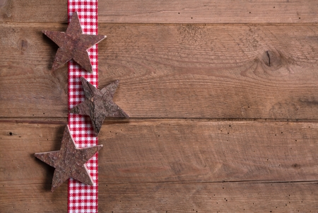 Wooden Christmas stars on checkered ribbon on wooden for a greeting card photo