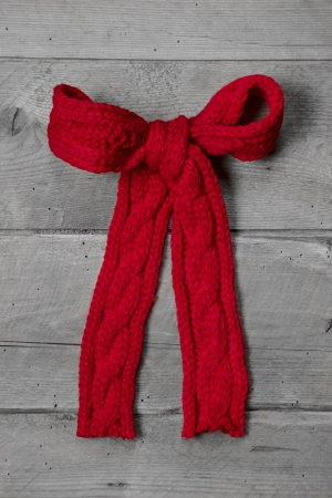 Red knitted bow for a present on grey wooden - greeting card for christmas or birthday