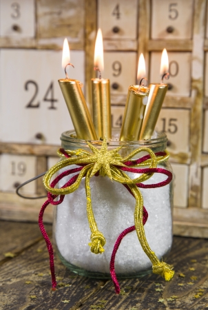Four golden candles -  traditional christmas decoration with wood - with a calendar photo
