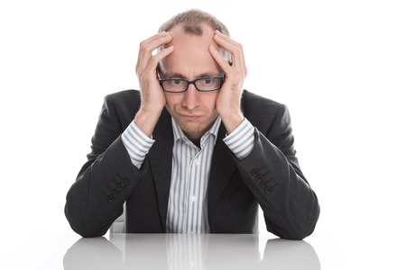 disappointed: Frustrated businessman wearing glasses sitting at desk with head in hands isolated on white background Stock Photo
