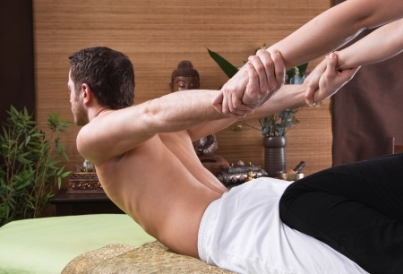 women body: Hands of woman making massage - man at spa - time for relax