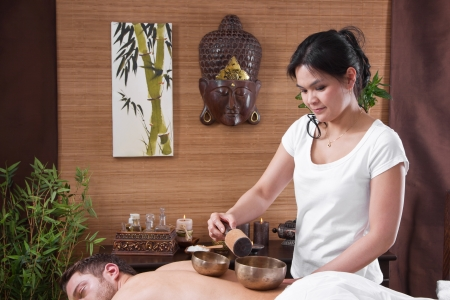 tibetan singing bowl: Hands of woman making massage - man at spa - time for relax with a singing bowl Stock Photo