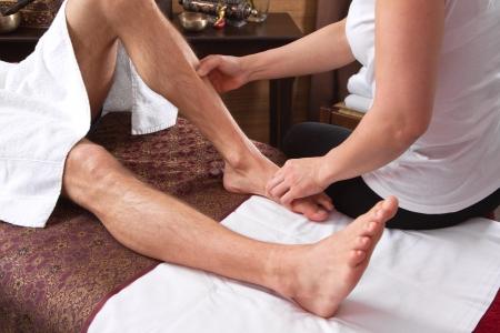 Hands of woman making massage - man at spa - foot massage photo