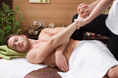 Man in a thai massage salon - traditionel healtcare - stretching photo