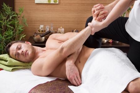 hands massage: Man in a thai massage salon - traditionel healtcare - stretching Stock Photo