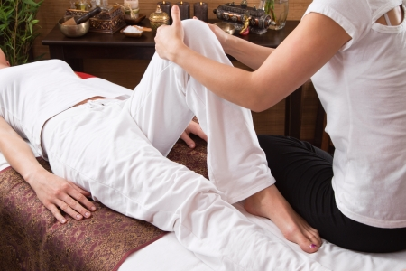 tense: Hands of a woman making foot massage - stretching and time for relax