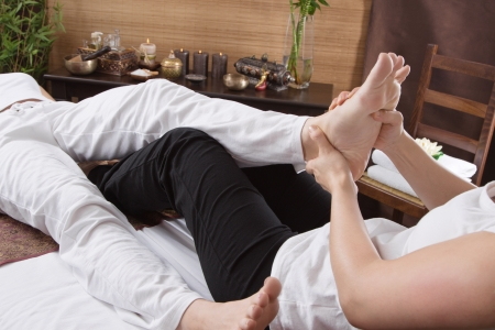 Hands of a woman making foot massage - stretching and time for relax photo