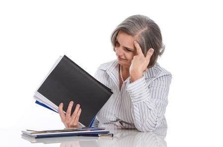 Overwerkt: grijs haired vrouw gewezen op het werk op een witte achtergrond - tijd voor pensioen Stockfoto