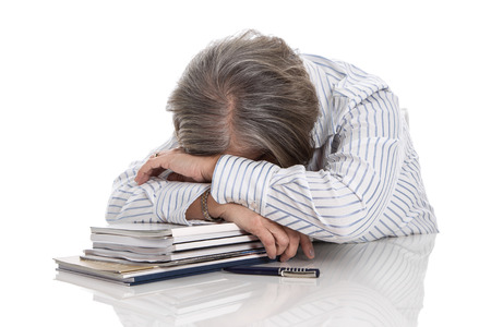 Grijze haren vrouw slapen op boeken - overwerkt op een witte achtergrond - burn-out