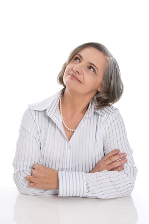 50 to 60: Senior grey haired woman folding arms and fond memories, dreaming isolated on white background Stock Photo