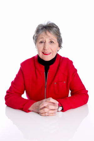 golden ager: Portrait of old lady with grey hair in red jacket isolated on white background - golden age Stock Photo