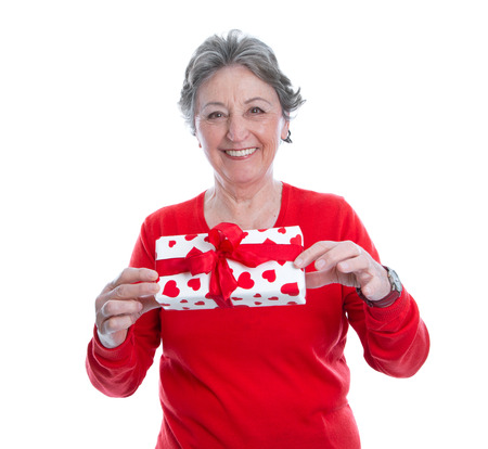 grey haired: Smiley grey haired woman in red holding present isolated on white background - valentines day, christmas or birthday gift Stock Photo