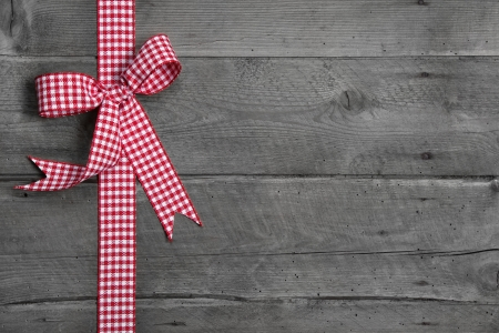 compliments: Grey wooden background with red and white checkered bow as border - idea for a festive rustic advertising board Stock Photo