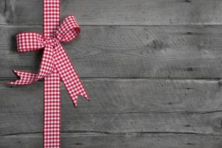 Grijze houten achtergrond met rode en witte geruite strik als grens - idee voor een feestelijke rustieke reclamebord