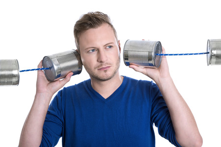 disadvantages: Stressed man overworked holding tin can phones isolated on white background - decision Stock Photo