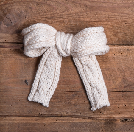 White knitted woolen bow on square wooden background - voucher or coupon for christmas photo