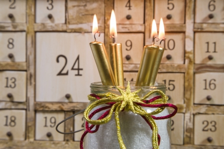 Shabby chic advents calendar with four gold burning candles - atmospheric for christmas photo