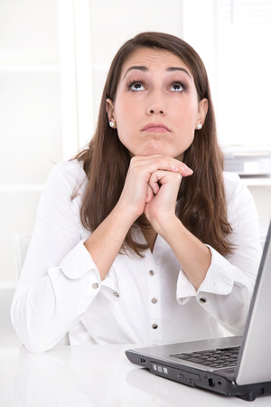 ennui: Bored businesswoman at desk looking up from laptop - day dreams