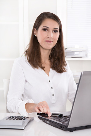 likable: Young smiling businesswoman at desk in a bank - consulting at a specialist Stock Photo