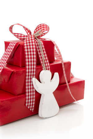 Red christmas presents with a white wooden angel an red checkered ribbon isolated in Country style photo