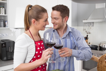 Couple celebrate love - cooking together in the kitchen and have fun - drinking red wine photo