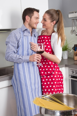 Couple in love cooking together in the kitchen and have fun - drinking red wine photo