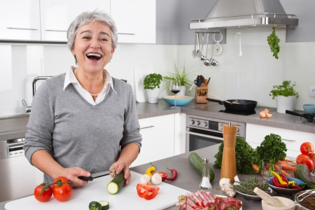 Senior or older woman with grey hair cooking in kitchen - vegetables photo