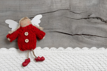赤のクリスマスやグリーティング カードのための灰色の木製の背景に守護天使