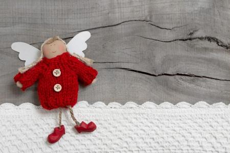 angel de la guarda: Navidad roja o guardián ángel en fondo gris de madera para una tarjeta de felicitación