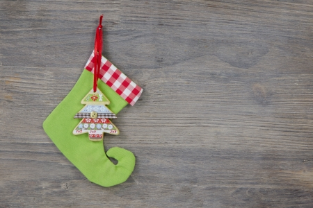 Green santa boots on a shabby wooden background for a christmas card photo