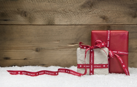 december: Red and white Christmas presents, with snow on wooden background for a greeting card or coupon in country or shabby chic style Stock Photo