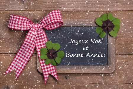 Chalk board with Merry Christmas message , santa and snowflakes on wooden background in french with a red checkered ribbon with text photo