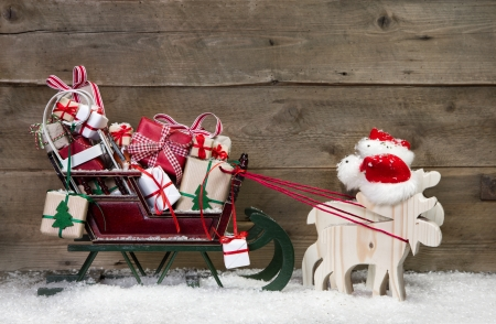 Christmas card decoration: elks pulling santa sleigh with presents on a wooden background - funny greeting card in Country Style  Stock Photo