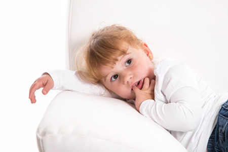 shy girl: Cute child - shy girl lying on white sofa sucking thumb or finger - strawberry blonde