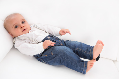 Cute baby lying barefoot on white sofa wearing blue denim jeans - alone and sad photo