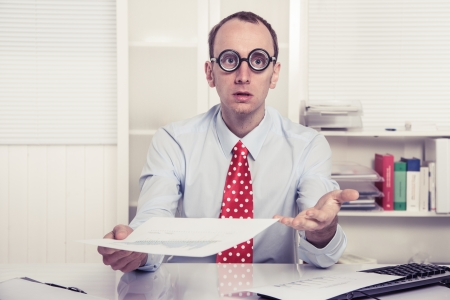sell: Businessman - hard sell or perplexed handing paper over - stressed man at work - high IQ Stock Photo