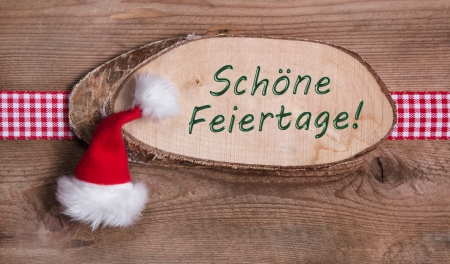 Wooden sign with Merry Christmas message and checkered ribbon and a santa hat on a wooden board photo
