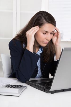 Burnout: überarbeitet müde Geschäftsfrau in blauen Kopf kratzen am Schreibtisch mit Laptop und Taschenrechner - Kopfschmerzen